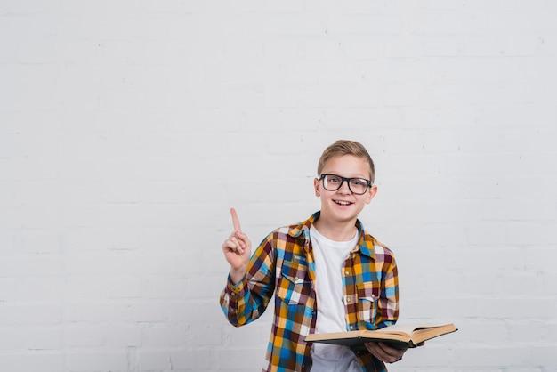 Портрет улыбающегося мальчика с очками, держа в руке открытую книгу, указывая пальцем вверх Premium Фотографии