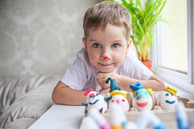 장식 된 부활절 달걀 앞 창턱에 누워 그린 얼굴로 웃는 4 살짜리 소년의 초상화 프리미엄 사진