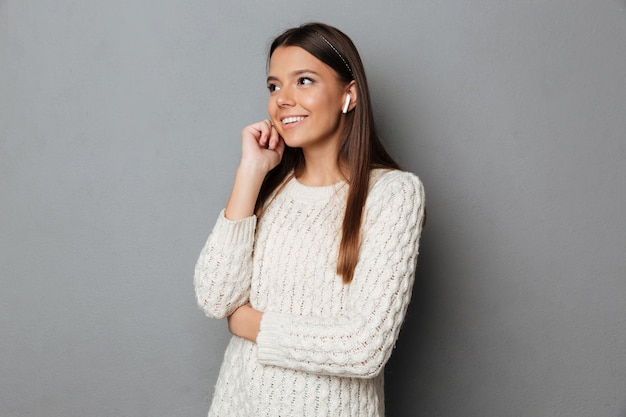 ワイヤレスイヤホンを使用してセーターで微笑んでいる女の子の肖像画 無料写真