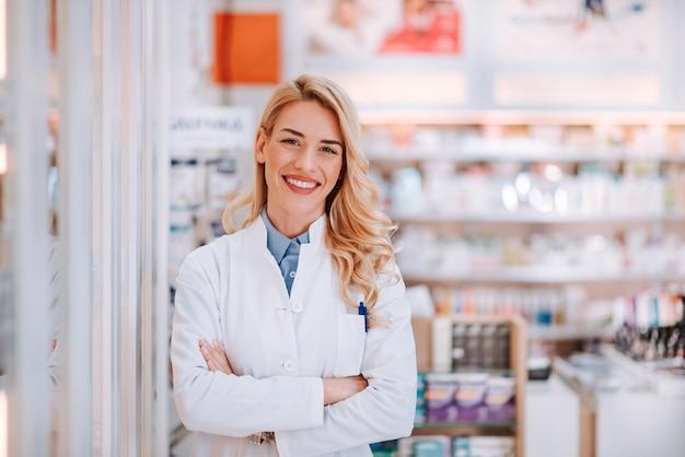 Портрет усмехаясь работника здравоохранения в современной аптеке. Premium Фотографии