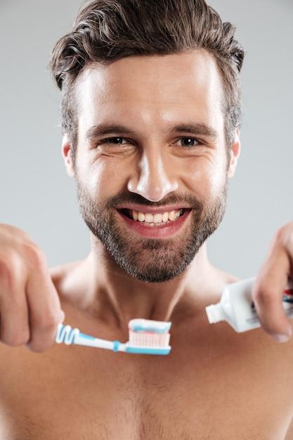 歯ブラシに歯磨き粉を入れて笑みを浮かべて男の肖像 無料写真