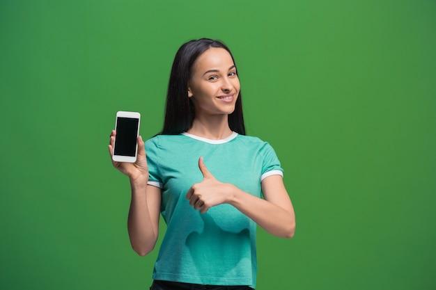 Портрет улыбающейся женщины, показывающей пустой экран смартфона, изолированный на зеленом фоне Бесплатные Фотографии