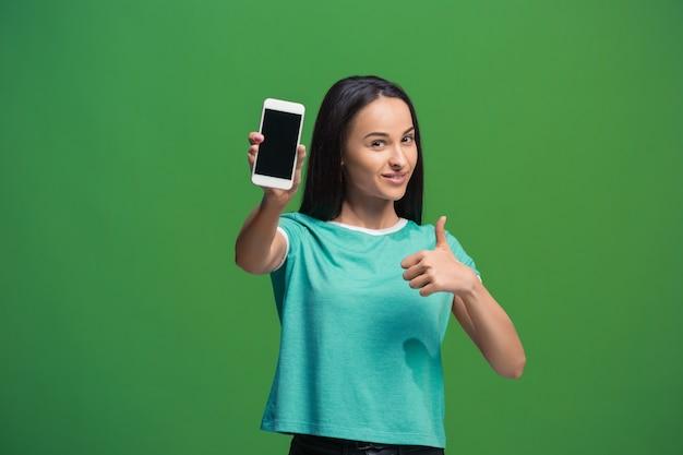 그린에 고립 된 빈 스마트 폰 화면을 보여주는 웃는 여자의 초상화 무료 사진