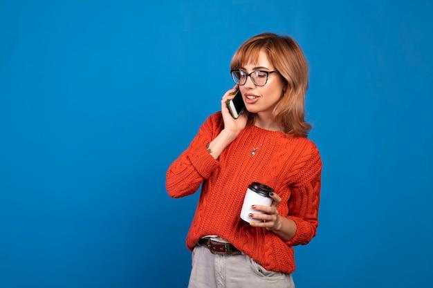 Портрет улыбающейся молодой случайной женщины разговаривает по мобильному телефону, изолированному на синем фоне. Premium Фотографии
