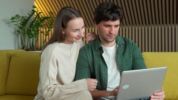 집에서 노란색 소파에 앉아있는 동안 노트북을 사용하는 웃는 젊은 부부의 초상화 프리미엄 사진