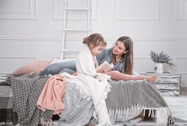 Портрет улыбающейся молодой милой матери и дочери, читающей книгу, лежа и расслабляющуюся в постели в яркой большой белой комнате. Premium Фотографии