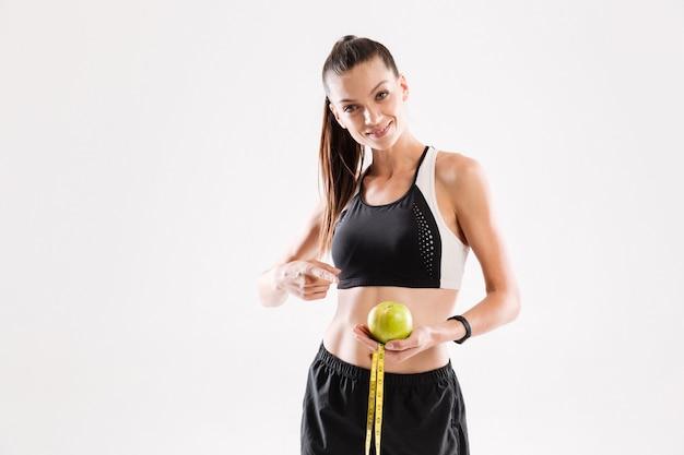 青リンゴを保持している笑顔の若いフィットネス女性の肖像画 無料写真