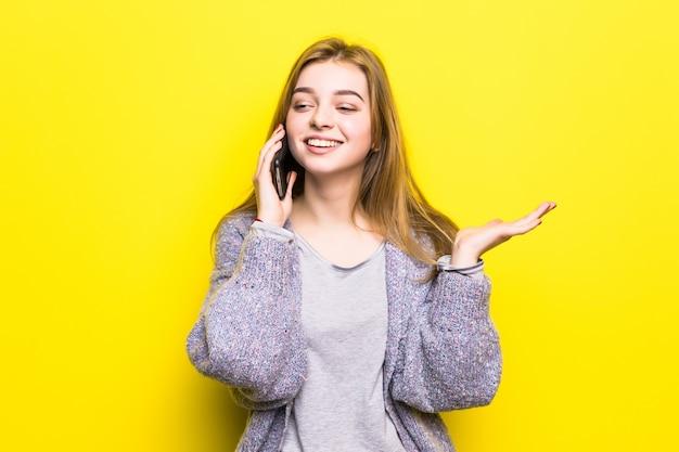 Портрет улыбающейся молодой девушки-подростка с брекетами, говорящей по мобильному телефону изолированы Бесплатные Фотографии