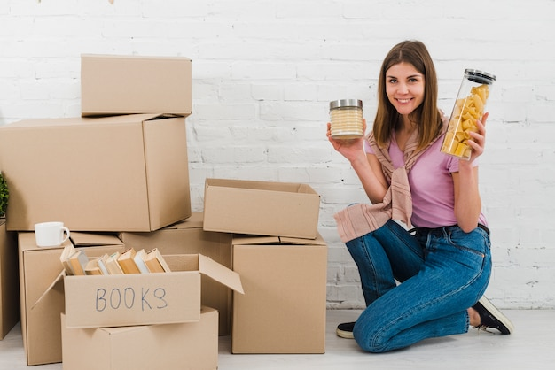 Портрет улыбающегося молодой женщины, держащей бутылки с закусками на коленях возле груды картонных коробок Бесплатные Фотографии