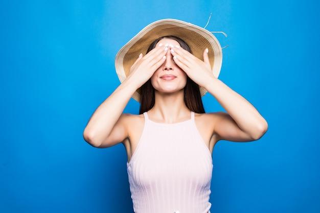 Портрет улыбающейся молодой женщины в летней шляпе, закрывающей глаза руками, изолированными над голубой стеной. Бесплатные Фотографии