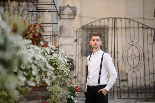 旧市街を背景にスタイリッシュな男のクローズアップの肖像画。 Premium写真