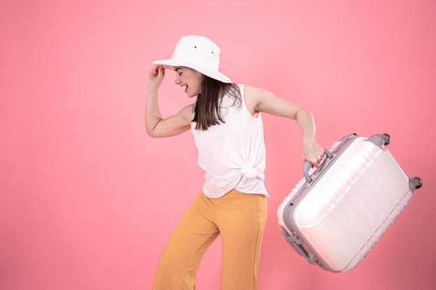 旅行のためのスーツケースとおしゃれな夏服とピンクの白い帽子のスタイリッシュな女性の肖像画。 無料写真