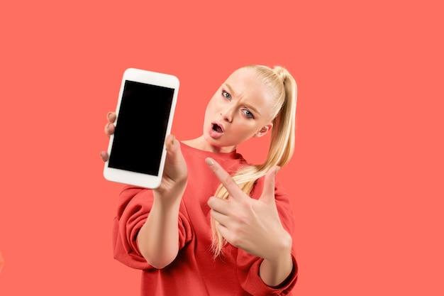珊瑚の背景の上に分離された空白の画面の携帯電話を示す驚き、笑顔、幸せ、驚きの少女の肖像画。 無料写真