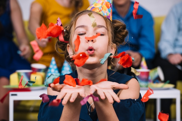 Portrait of a teenage girl blowing confetti on her birthday Free Photo