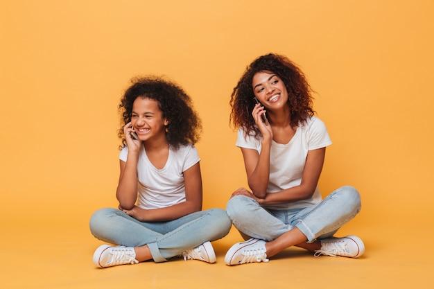 Pohoneで話している2人の陽気なアフロアメリカンの姉妹の肖像 無料写真