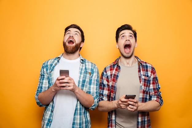 携帯電話を保持している2人の興奮した若い男性の肖像画 Premium写真