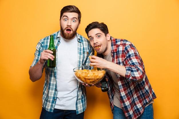 Портрет двух потрясенных молодых людей, пьющих пиво Premium Фотографии