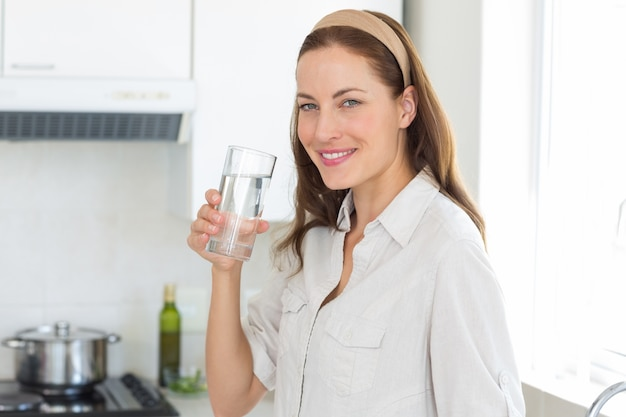 Portrait of a woman drinking water in kitchen Premium Photo