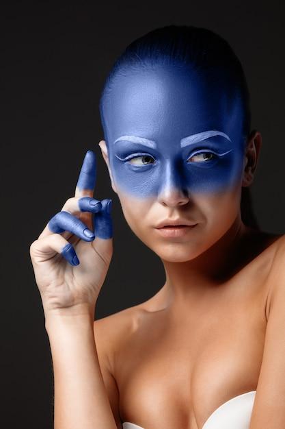 青いペンキで覆われたポーズをとっている女性の肖像画 無料写真