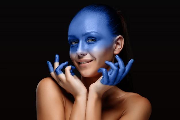 Портрет женщины, которая позирует покрыта синей краской Бесплатные Фотографии