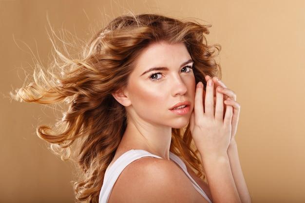 彼女の顔の近くに彼女の手を持つ女性の肖像画 Premium写真
