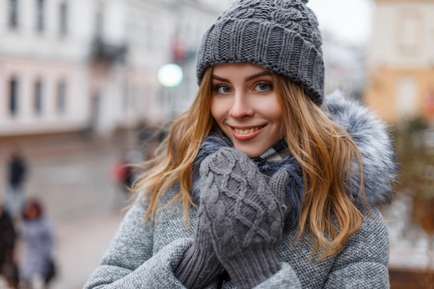 街の通りのスタイリッシュなコートのニットミトンのニット帽で甘い笑顔で自然なメイクで美しい青い目を持つ素晴らしい若い女性の肖像画。幸せな女の子。 Premium写真