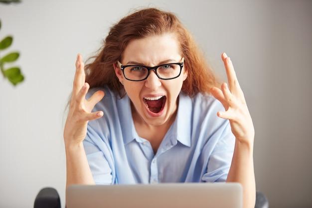 Портрет молодой привлекательной деловой женщины с разочарованным взглядом, работающей на ноутбуке Бесплатные Фотографии