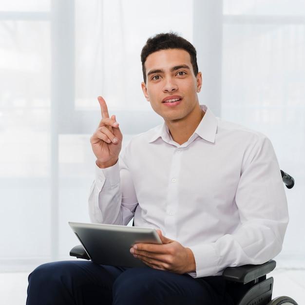 デジタルタブレットを手で保持している車椅子に座っている若いビジネスマンの肖像画 無料写真