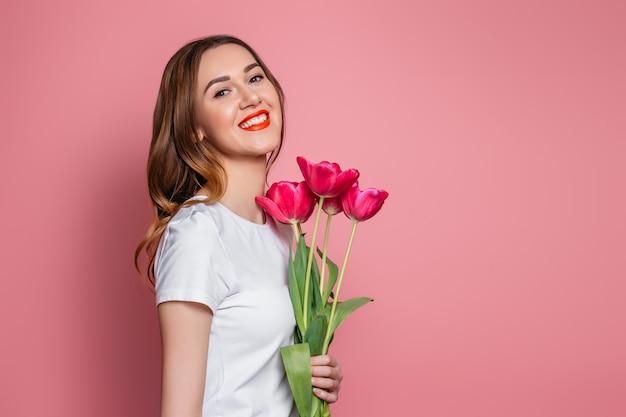 チューリップの花束を持って、ピンクの背景に分離された笑顔の少女の肖像画 Premium写真
