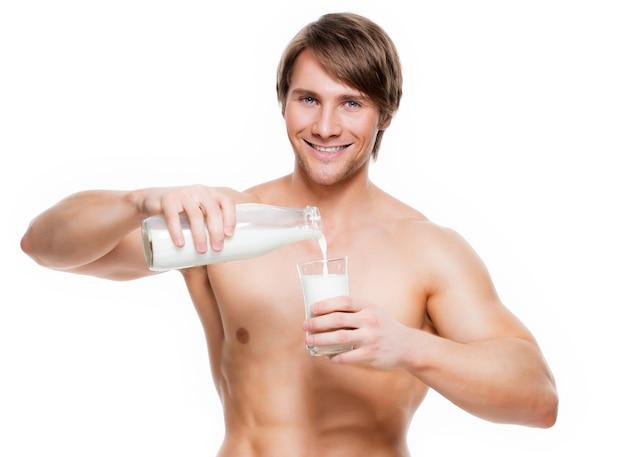 ガラスに牛乳を注ぐ若いハンサムな筋肉の男の肖像画-白い壁に隔離。 無料写真