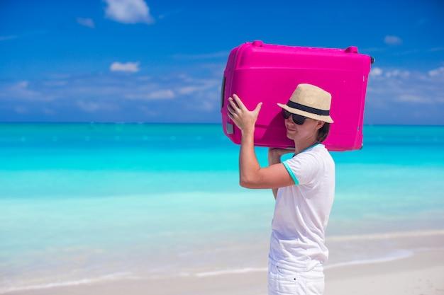 Портрет молодого человека с багажом на пляже Premium Фотографии