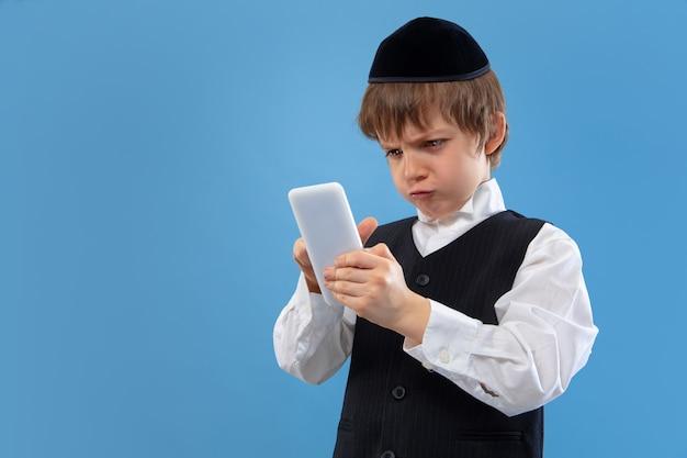Портрет молодого ортодоксального еврейского мальчика изолированного на голубой студии Бесплатные Фотографии
