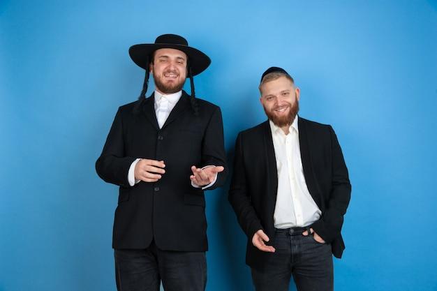 Портрет молодых православных еврейских мужчин, изолированных на синей студии Бесплатные Фотографии