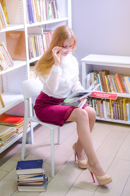 Портрет молодой красивой женщины, чтение в библиотеке Premium Фотографии