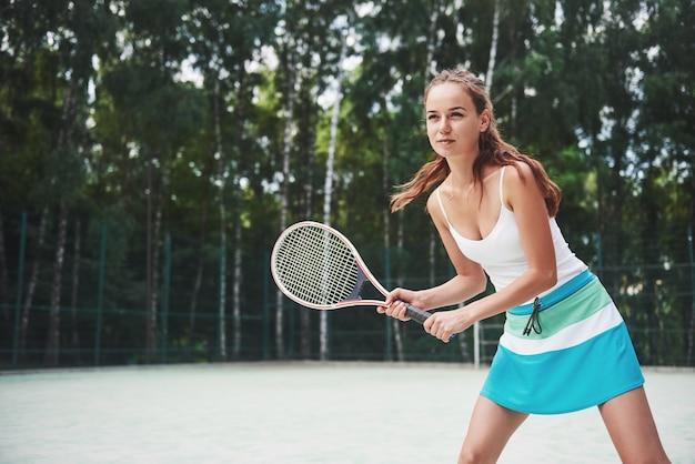 サーブの準備ができて立っている若いテニス選手の肖像画。 無料写真