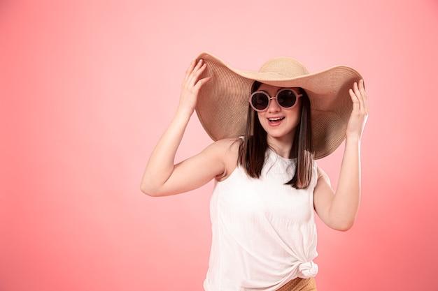 大きな夏の帽子とメガネ、ピンクの背景の若い女性の肖像画。夏のコンセプトです。 無料写真