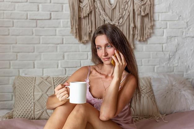집에서 침대에 앉아있는 동안 스마트 폰을 사용하여 분홍색 잠옷에 젊은 여자의 초상화. 친구와 채팅. 온라인 개념 쇼핑. 편안하고 뜨거운 커피 또는 차 한잔. 프리미엄 사진