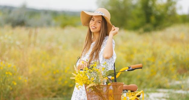 帽子をかぶっている若い女性の肖像画は夏の時間にフィールドの彼女の自転車の近くに立っています。 Premium写真