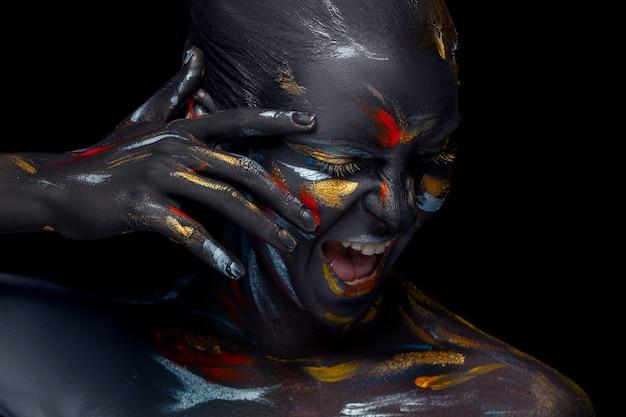Портрет молодой женщины, которая позирует покрыта черной краской Бесплатные Фотографии