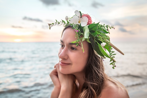 日没時の海を背景に頭に花の構図を持つ若い女性の肖像画。 無料写真