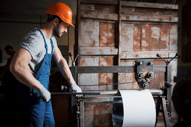 Портрет молодого рабочего в каске на большом металлообрабатывающем заводе. Бесплатные Фотографии