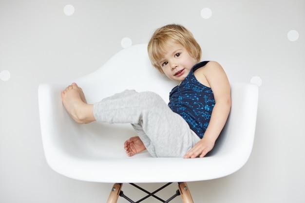 Портрет очаровательного босоногого ребенка со светлыми волосами, одетого в серые брюки и рубашку без рукавов, наслаждающегося детскими развлечениями в помещении, сидящего на белом стуле, выглядящего счастливым и радостным. Бесплатные Фотографии