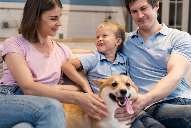 Портрет очаровательной семьи, играющей с собакой Premium Фотографии