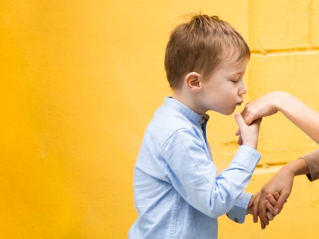 Портрет прелестный молодой мальчик, целуя руку матери Бесплатные Фотографии