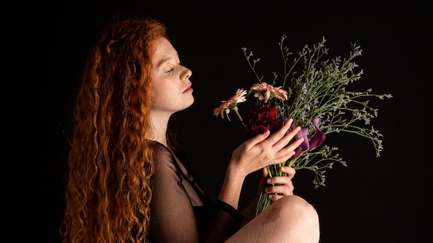 色とりどりの花を持つ大人の女性の肖像画 無料写真