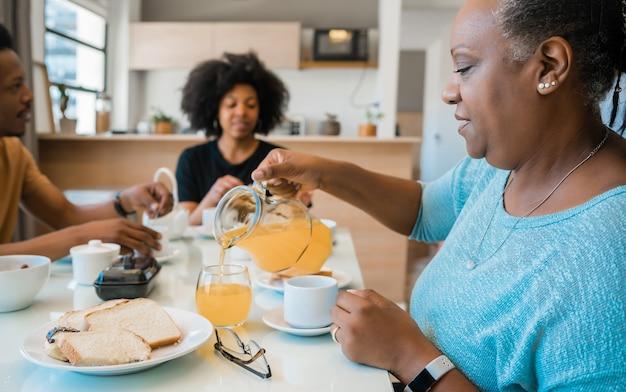 家で一緒に朝食を持っているアフリカ系アメリカ人の家族の肖像画。家族やライフスタイルのコンセプトです。 無料写真
