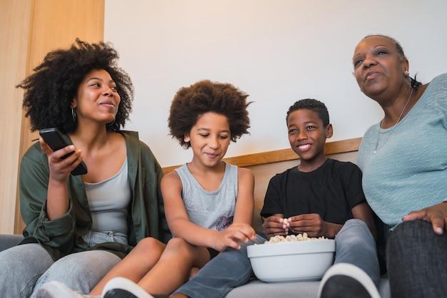 アフリカ系アメリカ人の祖母、母親と子供たちが映画を見て、自宅のソファーに座っている間ポップコーンを食べているの肖像画。家族やライフスタイルのコンセプトです。 無料写真