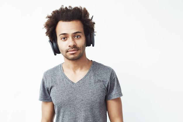 ストリーミング音楽サービスを聞いてビートの白い壁を楽しんでいるワイヤレスヘッドフォンでアフリカ人の肖像画。 無料写真