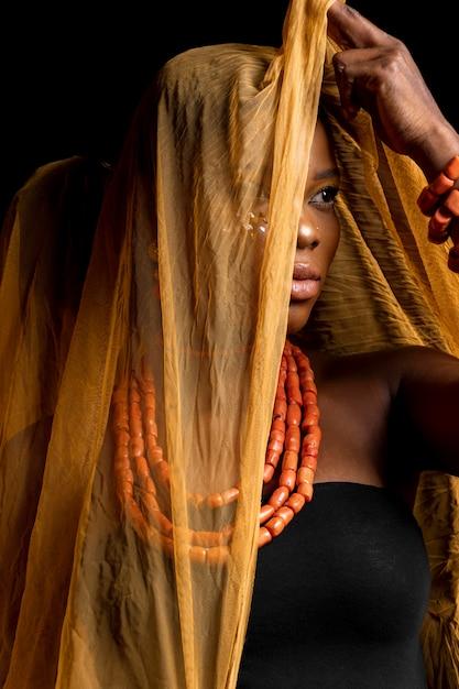 伝統的なアクセサリーと黄色のベールを身に着けているアフリカの女性の肖像画 無料写真