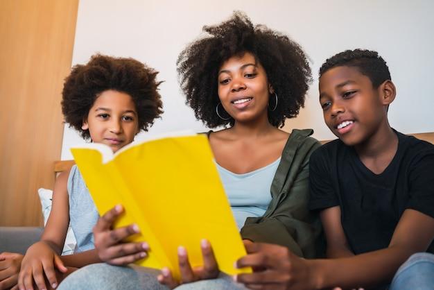 自宅で子供たちに本を読んでいるアフロアメリカンの母の肖像画。家族やライフスタイルのコンセプトです。 無料写真